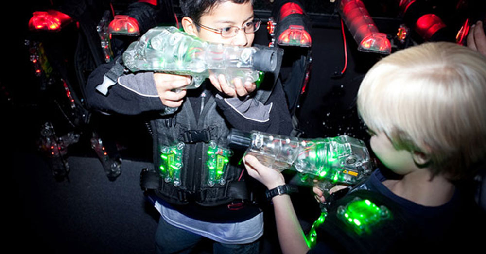 Two boys at a laser tag arena aiming