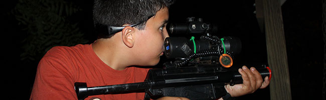 Young boy aiming his laser tag gun