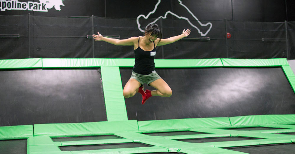 A woman enjoying jumping at a trampoline park.