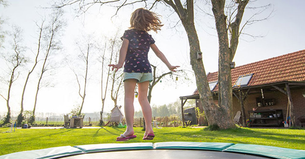 Girl Jumping on a Trampoline in the Sun