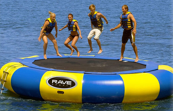 Kids wearing life jackets on a floating trampoline