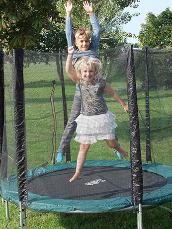 Youngsters Jumping on a Netted Trampoline